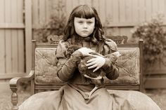 VINTAGE:  Little girl all dressed in fancy dress and posed with her beloved pet chicken.