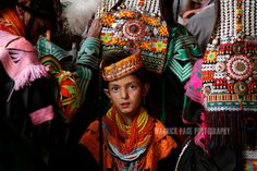 """KALASHA VALLEYS, PAKISTAN - MAY 15: A Kalash girl stands amongst women praying and telling historical stories during the """"Joshi"""" (spring) festival in the village of Batrik May 15, 2008 in the Kalasha Valleys, northwestern Pakistan. The Joshi Festival is a celebration of dance, music and prayer to welcome the coming of warmer season and the new life and crops it brings. The shrinking Kalash community of 4000, who claim to be descendants of Alexander the Great and worship several gods, are…"""