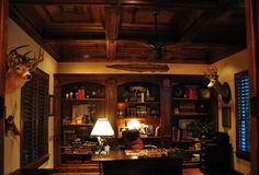 A dramatic, masculine effect was achieved by darkening the stain on the furniture and coffered ceiling. The book shelf décor was arranged for a working unit that is pleasing to the eye