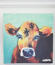 "Let this Sweet Baby Cow Canvas Print brighten your farmhouse décor. There's something grounding and peaceful about these farm animals, and this girl's lovable face, with the colorful turquoise background, will surely add cheer to any room. Stretched canvas on wooden frame. 12"" square"
