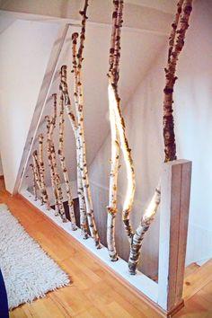 Kreatives Treppengeländer. Äste als Trennwand und Dekoelement für die Treppe. Indirekte Beleuchtung.