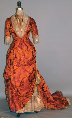 PURPLE & ORANGE SILK BUSTLE GOWN, 1878-1883 2-piece silk brocade, purple w/ orange flowers & foliage, long fitted bodice, trimmed w/ taupe satin & lace; draped skirt front, very long train.