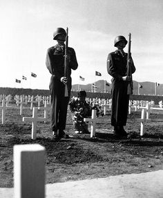 A little Korean girl places a wreath of flowers on the grave of an American soldier, while Pfc. Chester Painter and Cpl. Harry May present arms, at the United Nations cemetery in Pusan. April 9, 1951. Cpl. Alex Klein. (Army)