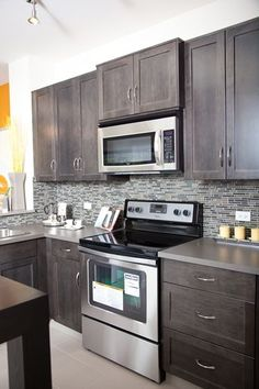 Stylish modern kitchen with dark shaker style maple cabinets, stainless steel appliances and glass mosaic tile backsplash. At Prospect Rise townhomes by Avi Urban.
