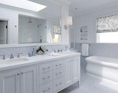 white double bathroom vanity, blue mosaic tiles backsplash, marble herringbone tiles floor, white rectangular bathroom mirror, double sinks, freestanding tub, rain shower head, subway tiles shower surround and blue custom roman shade.