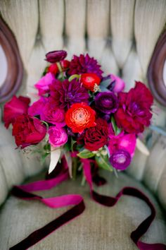 A bouquet of ranunculi, roses, and dahlias bouquet in shades of red and fuchsia