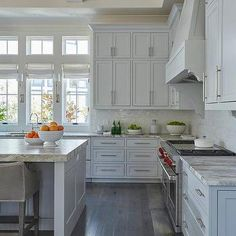Light Gray Stacked Kitchen Cabinets with Rustic Wood Floors