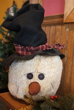 This snowman was made out of chenille and a little tea or distressing ink was sprayed on to give it that aged look. The hat is made out of felt with a swatch of fabric tied around it.
