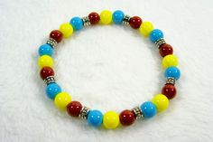 This Black and African Pride stretch bracelet utilizes the colors of the African country Chad's flag (blue, yellow, red). The round 8mm glass beads are accented with silver, metal, drum-shape…