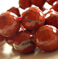 12mm Micro Faceted Red Jasper Round Beads,, full strand, 15.5  Classic, gorgeous red jasper is, as you know, an orange-y brick red. These have some banding as shown in first photo, adding even more interest and style. See second photo to get a look at a typical strand (they look even better in person!)