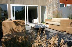 overzicht van moderne tuin met multifunctionele tuintafel.