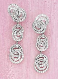A Rare Pair of Diamond Earpendants CARTIER circa 1950 Designed as a series of graduated circular and baguette-cut Diamond spiralmotifs,mounted in Platinum , length 8.4 cm. Signed 'MontureCARTIER.' with jeweler'smark and numbered. with French assaymarks