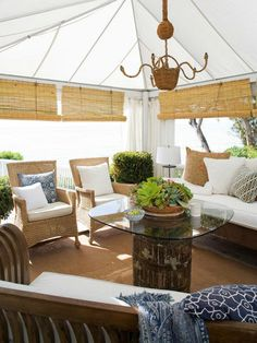 Coastal outdoor cabana style space with teak and wicker seating, white cushions and blue throw pillows
