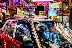 """Neon Taxi. These ubiquitous taxicabs are an iconic element of the supercity. I tried to capture as many """"HK elements"""" as I could in this one picture by getting up close to the vehicles in the foreground, and having the neon signages in the background and also on the windshield. 1/320 sec at f/6.8, ISO 3200. Leica SL , Leica Summilux-M 35mm Aspherical. Hong Kong, China. July 2016. © Jon She"""