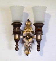 Home Interiors Mediterannean Wood and Brass Wall Sconces    Brand: Home Interiors, Homco  Height: 9.5 inches (with glass inserts)  Width: 7 inches  Depth: 4.25 inches  Color: Brown and Gold  Material: Wood and Brass With Glass Inserts  This decorative pair of sconces made by Home Interior was acquired from a distributor and is no longer available from Homco. Mediterannean style features a double base with center spray of foliage. Sconce includes two frosted peg votive holders.