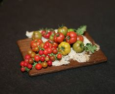 Cutting board with different tomatoes, miniature completely handmade, with great attention to details to get the most realistic possible. Used materials: wood, polymer clay, paper, fabbric. Misura: 4,5 cm wide. deep 3,3, high max 1,7 cm. Tagliere con pomodori differenti , in