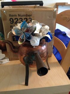 First attempt at my centerpieces. I made the flowers out of maps, sheet music, and fabric for the roses. Picture is property of Jessica A. Reese