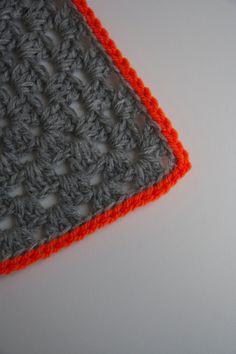 Grey granny square blanket with neon orange.   Piece ofa cookie etsy