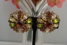 Hobe Vintage Rhinestone Earrings featuring Greens and Brown Colors Set in Goldtone & Signed. Price $36. These gorgeous rhinestone signed earrings are set in goldtone. Free Shipping to the United States. A great gift for Mother's Day and a perfect addition to your collection. To learn about Hobe, please read about him on our blog at www.CCCsVintageJewelryBlog.com. Have an amazing day. And don't forget that Mother's Day is coming up quickly as far as the mail. Best, Coco