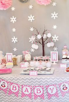 White tulle poms by Fizzy Party.  a pink and gray winter baby shower's dessert table with snowflake backdrop
