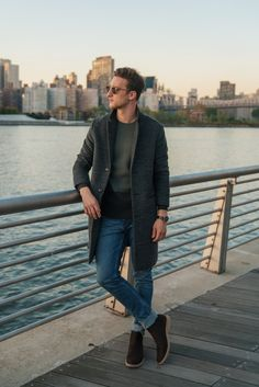 Marcel from One Dapper Street wears a wool-blend coat with a fitted sweater, cuffed jeans, and leather boots for a polished cold-weather weekend look.
