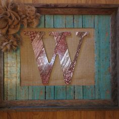 Monogram wooden letter mod-podged with scrapbook paper layered on burlap covered canvas in frame. Added burlap rosettes to decorate. Made by Connie :)