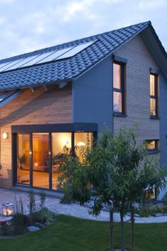 Lots of light in every day and time of year: Here a family has realized their dream of an ecological house in nature. Interesting facade design with slabs and Douglas fir cladding Terrace with wooden and glass roof pergola Generous corner glazing Terrasse Design, Planter Beds, House In Nature, Roof Structure, Backyard, Patio, Day And Time, Glass Roof, Facade Design