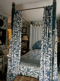 blue and white floral bed drapes with gingham lining in this adorable English bedroom