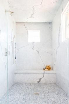 Walk into a large master bathroom shower to admire thin gray marble herringbone floor tiles and marble slab walls featuring stacked shower niches and a marble shower bench. Source by Master Bathroom Shower, Shower Niche, Bathroom Showers, Bathroom Ideas, Shower Ideas, Carrara Marble Bathroom, Bathroom Renovations, White Marble Bathrooms, Small Bathroom