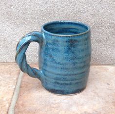 I threw this mug on my pottery wheel using strong white stoneware clay, added a fun twisty handle, and finished it in a lovely dark aquamarine blue reactive glaze. Dimensions--8cm across the rim and 10cm tall. The cup holds 450ml...weight 415gms Foodsafe glazes....dishwasher, oven and microwave safe.  I am happy to post anywhere---contact me for more specific prices, and I offer a combined shipping discount....applied at checkout. Thanks for looking. Whilst you are here, maybe youd like to…