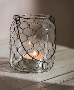Chicken-wire wrapped jar as votive candle holder with wire handle, posted by Ana Rosa Votive Candle Holders, Candle Lanterns, Diy Candles, Candle Jars, Candle Containers, Mason Jar Crafts, Mason Jars, Chicken Wire Crafts, Primitive Crafts