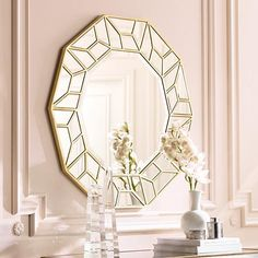 Faceted mirrors surround this polygon wall mirror in a gold finish