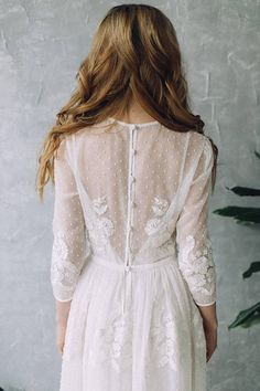 Perfect wedding dress in warm white color. Floor-length dress made of translucent chiffon in polka dots. 3/4 sleeves embroidered with lace, buttons at the cuffs. Top of dress made on the figure, embroidered with lace appliques, buttons on the back. The fluffy skirt is embroidered with