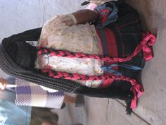 Many women in rural villages surrounding Oaxaca still dress in traditional clothing. Long tresses with satin ribbons and this  rebozo (shawl) on her head are typical for her village near Tlacolula.