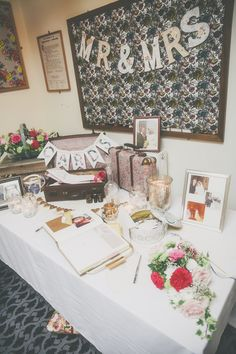 Guest book table - Image by  Millie Benbow Photography - A Phase Eight wedding dress for a vintage inspired village hall wedding with handpicked wild flowers and floral bridesmaid dresses.