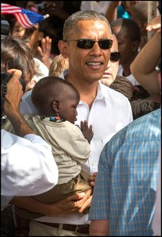 Pres. Obama holds a baby during his tour of Goree Island in Senegal Dakar.