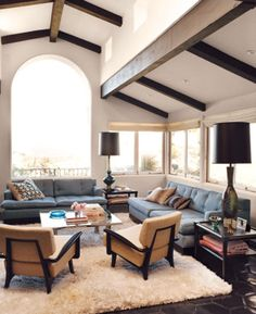 Exposed beams and floor to ceiling windows in this cozy space. | http://domino.com