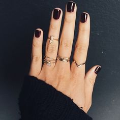 dark manicure., short nails, multiple rings