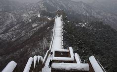 Turistas enfrentam a neve e o frio para caminhar pela Muralha da China.