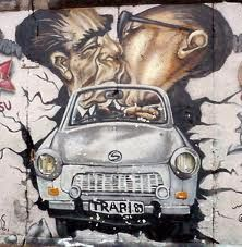 East side gallery at the former Berlin Wall  ( 1961 -1989 ) Picture of Brezjnev & HONECKER kissing in front a Trabant ( GDR car )