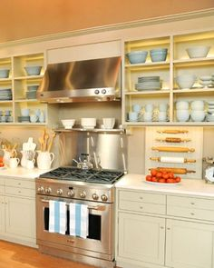 Martha Stewart studio kitchen - love the oven, stainless steel backsplash, rangehood, rolling pin display and open storage display of bowls, also the small round handles and colour of cupboards.