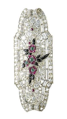 AN ART DECO RUBY, ONYX AND DIAMOND BROOCH  The tapered rectangular-shaped plaque set throughout with single and circular-cut diamonds, to the central floral motif set with ruby and emerald flowerheads and onyx leaves, mounted in platinum, circa 1925, 5.8 cm long