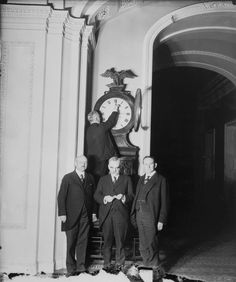 Senate Sergeant at Arms Charles Higgins turns forward the Ohio Clock for the first Daylight Saving Time, while Senators William Calder (NY), William Saulsbury, Jr. (DE), and Joseph T. Robinson (AR) look on, 1918.