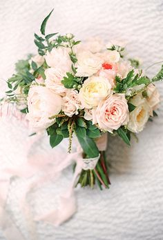 A loose wedding bouquet arrangement with champagne, blush, and ivory roses, peonies, and sprigs of fresh mint by @bpaperdesign   Brides.com