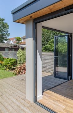 Residential extension | corner opening | flat roof overhang detail with spot lights | inside outside space | timber flooring / decking | aluminium bi-fold doors | hidden structure | concealed drainage