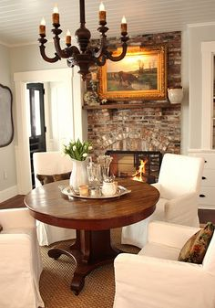 Cottage Chic Kitchen Eating Area. Love the brick just off the kitchen, round table from For Love of a House...love the Slipe Covered Chairs!
