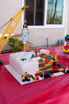 Lego cake. White cake with one corner cut out and filled in with chocolate Lego bricks. Lego men, crane and front loader are real legos.