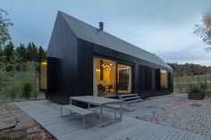 format elf nestles dark barn-shaped houses into bavarian forest - designboom | architecture
