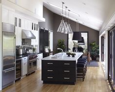 Two contrasting cabinet & island colors, gray accent walls, and sliding barn door