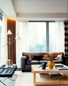 Modern Classics in a Manhattan Living Room  In a new 37th-floor Manhattan apartment, designers David Greer and Andrew Halliday mixed modern classics — a Karl Springer coffee table, a Jean-Michel Frank–style sofa, and Barcelona stools by Mies van der Rohe that the owner's Cavalier King Charles Spaniel, Emma, claims for her own.